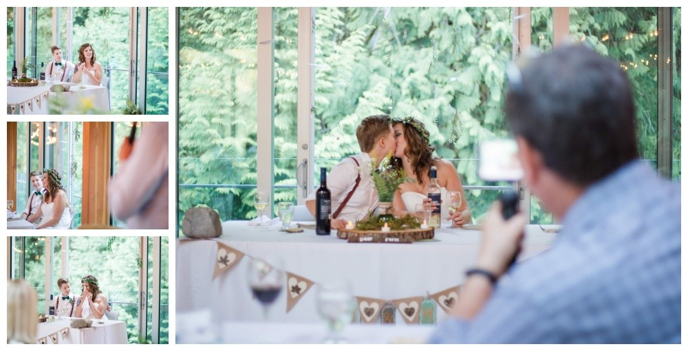Brides kiss at their head table after their forest wedding