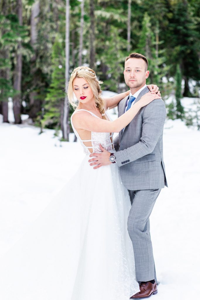 Bride and groom pose for photos in the snow during their Vancouver Island Winter Elopement