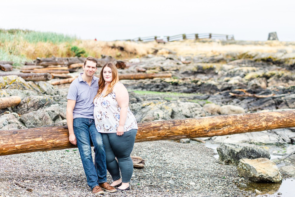Couple leaning on a log on a rocky vancouver island beach in oak bay