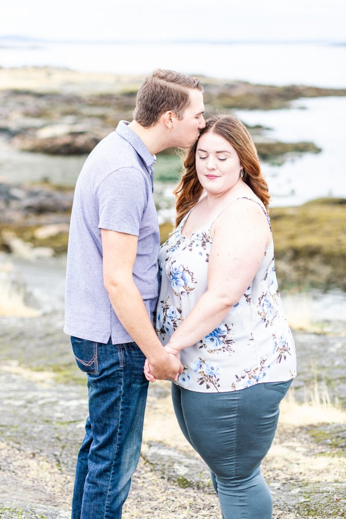 Man kisses side of womans face on the beach. Victoria Engagement Photographer
