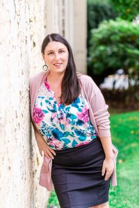 Image of Nanaimo Photographer Meaghan Harvey in a pink sweater leaning against a wall