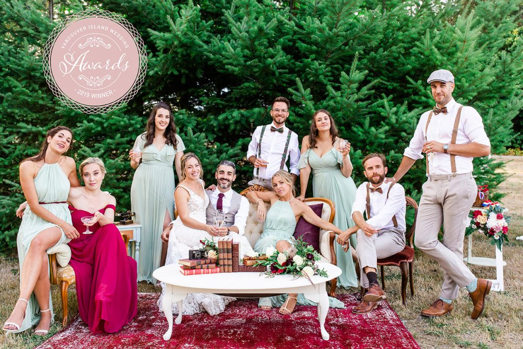 Bride and groom pose with their wedding party on a beautiful lounge set by Darling Vintage Rentals in Nanaimo
