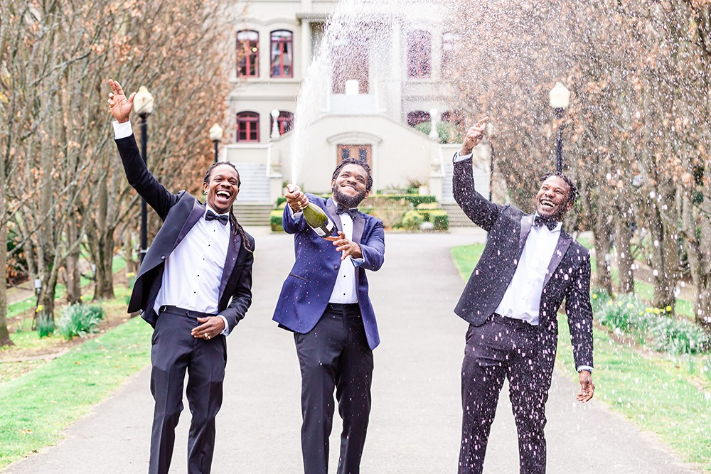 Groom and groomsmen celebrate by spraying a bottle of champagne on wedding day