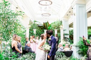 Bride and groom kiss during wedding processional at the Spring Prelude garden at Buchart Gardens